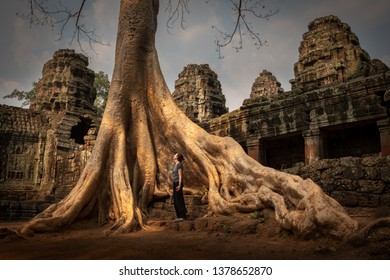SIEM REAP, CAMBODIA - MARCH 23, 2019: Woman admiring the huge tree roots at the overgrown Banteay Kdei temple in Angkor.