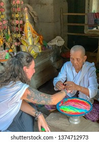 Siem Reap, Cambodia - March 26, 2019 :  Tourists receiving blessing from Buddhist nun in  temple in Angkor Complex in Cambodia.