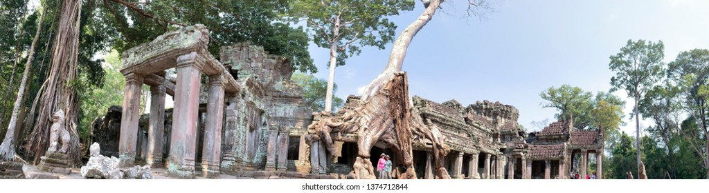 Siem Reap, Cambodia - March 27, 2019 :  Tourists at jungle overgrowth in ruins of Preak Khan temple in Angkor Complex in Cambodia.