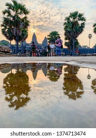 Siem Reap, Cambodia - March 27, 2019 :  Tourists reflecting in puddle of water  watching sunrise in Angkor Wat in Cambodia .