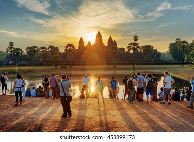 SIEM REAP, CAMBODIA - MAY 4, 2015: Tourists taking picture of ancient temple complex Angkor Wat at sunrise. The sun reflected in lake at dawn. Mysterious Angkor Wat is a popular tourist attraction.