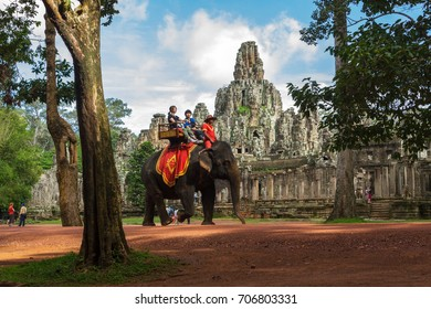 SIEM REAP, CAMBODIA - SEPTEMBER 1, 2015: Tourists ride elephants along the road around the Bayon temple at the Angkor Wat complex.