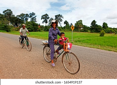 Siem Reap, Cambodia - September 13, 2013: Residents are passing by with a baby on a bike