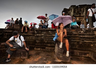 SIEM REAP, CAMBODIA-AUGUST 4, 2009. Many tourists on the top of one of the temples in Angkor wat, prepare their tripods and cameras to take a picture at sunset on August 4, 2009