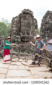 Siem Reap, Combodia - 22 May 2018: Asian couple tourist taking photo with smiling face stone in Bayon temple in Angkor Thom, Siem Reap province, Cambodia