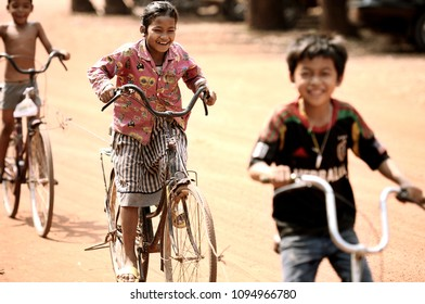 Siem Reap province, Cambodia - March 05, 2015 : Children cycling and have smile on the face on dirt roads in Siem Reap province, Cambodia.