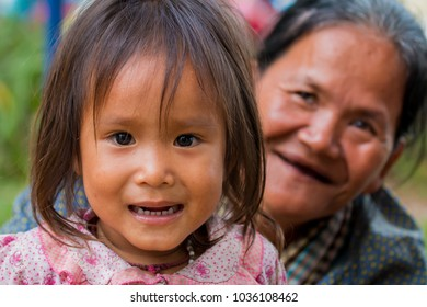 Siem Reap, Siem Reap Province, Cambodia - November 24 2015 : Portrait of a young girl and old woman at the Bon om Touk Water Festival on the Tonle Sap river in Siem Reap