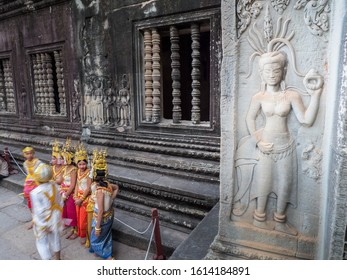 Siem Reap,Cambodia-Dec05'19: Stone carving of Apsara in Khmer culture style with blurred moving people who dress same as Apsara in Angkor Wat for taking photo with tourist.Focus at white stone Apsara.