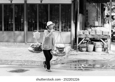 SIEM RIEP, CAMBODIA - SEP 28, 2014: Unidentified Khmer woman carries products to sell in Siem Reap. 90% of Cambodian people belong to Khmer etnic group
