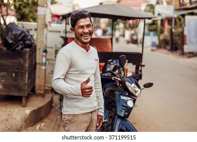 SIEMREAP, CAMBODIA - JAN 25, 2016: The local driver of tuk-tuk is smiling