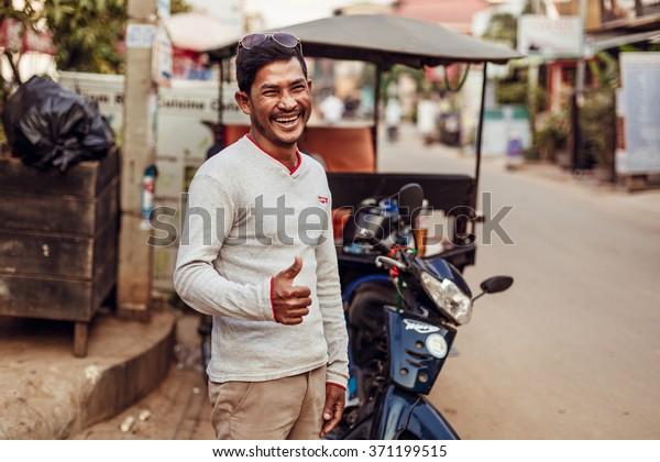 SIEMREAP, CAMBODIA - JAN 25, 2016: The local driver of tuk-tuk is smiling