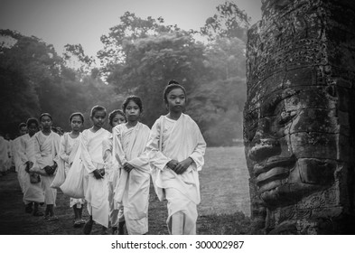 SIEMREAP, CAMBODIA - MAY 3 : Many unidentified Buddhist nuns girls in white suit walking for celebrate Buddhist Sabbath at Angkor wat at morning on May 3, 2015 in Siem Reap, Cambodia
