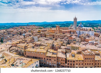 Siena cityscape in sunny day with the Siena Cathedral and the hilly tuscany in Italy