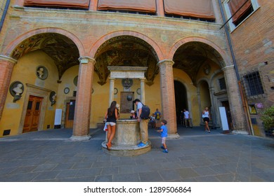 Siena courtyard, well (fount) Siena, Toscana / Italy. August 2017: tourists look into the well