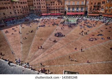 SIENA, ITALY - APR 6: Tourists walk in Piazza del Campo, April 6, 2013 in Siena, Italy. The historic centre of Siena has been declared by UNESCO a World Heritage Site.