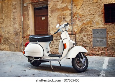 SIENA, ITALY - AUGUST 07, 2015: White Vespa retro motorbike at the old street of Siena, Italy. Vintage style.