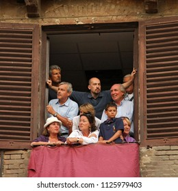 SIENA, ITALY - AUGUST 16, 2008: A group of people awaits the departure of the Palio di Siena overlooking the balconies in Piazza del Campo