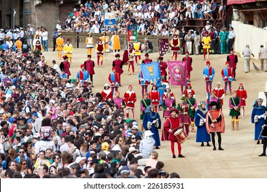 """SIENA, ITALY - AUGUST 16: Parade before start of annual traditional Palio di Siena horse race in medieval square """"Piazza del Campo"""" August 16, 2014 in Siena, Italy"""