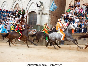 """SIENA, ITALY - AUGUST 16: Riders compete in horse race """"Palio di Siena"""" in medieval square """"Piazza del Campo"""" on August 16, 20014 in Siena, Italy. The race is held twice every year."""