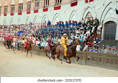 """SIENA, ITALY - AUGUST 16: Riders compete in horse race """"Palio di Siena"""" in  medieval square """"Piazza del Campo"""" on August 16, 20014 in Siena, Italy. The race is held twice every year"""