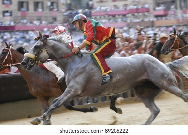 """SIENA, ITALY - AUGUST 16: Unidentified riders compete in the horse race """"Palio di Siena"""" in the medieval square """"Piazza del Campo"""" on August 16, 2007 in Siena, Italy. The race is held twice every year."""