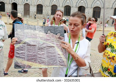 Siena, Italy - August 20, 2015: The guide Irina tells tourists about the Palio di Siena (horse race that is held twice each year)