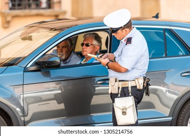 Siena, Italy - August 27, 2018: Street in old town village in Tuscany with closeup of people tourists getting fine ticket from carabinieri police officer for driving in ZTL zone