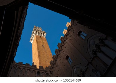 SIENA, ITALY - JAN 6, 2017: Torre del Mangia 87 m. bottom view (Tower of Mangia) on blue clear sky. Siena, Tuscany, Italy, Europe