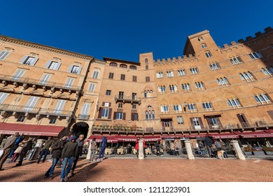 SIENA, ITALY - JANUARY 5, 2017: Tourists visit the ancient and medieval Piazza del Campo (Campo square) in the downtown of Siena, Toscana (Tuscany), Italy