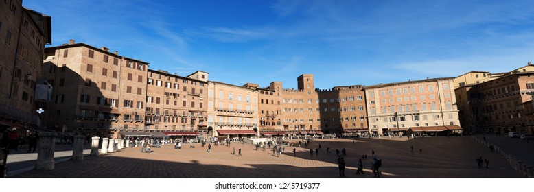 SIENA, ITALY - JANUARY 5, 2017: Tourists visit the ancient and medieval Piazza del Campo (Campo square) in the downtown of Siena, Toscana (Tuscany), Italy, Europe