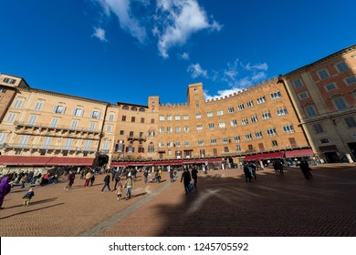 SIENA, ITALY - JANUARY 6, 2017: Tourists visit the ancient and medieval Piazza del Campo (Campo square) in the downtown of Siena, Toscana (Tuscany), Italy, Europe