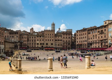 SIENA, ITALY - JULY 4, 2018 - Scenic view of Piazza del Campo with tourists in a cloudy summer day