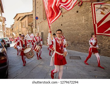 Siena, Italy - July 8 2017: People are marching through the street to celebrate the winning in Palio di Siena.