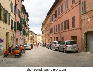 Siena, Italy - June 15, 2018 : Cars and motocycles parked along two side of Siena street with traditional old stone houses, Tuscany, Italy.