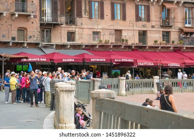 Siena, Italy - June 15, 2018 : A group tour of chinese tourists sightseeing at Campo Square (Piazza del Campo) in Siena, Tuscany, Italy.