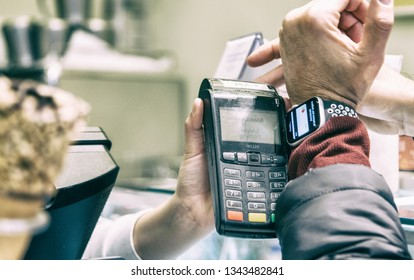 SIENA, ITALY - MARCH 17,2019: Man uses Apple Pay system with Apple Watch 4 to pay in a shop. Apple Pay is a mobile payment and digital wallet service by Apple Inc