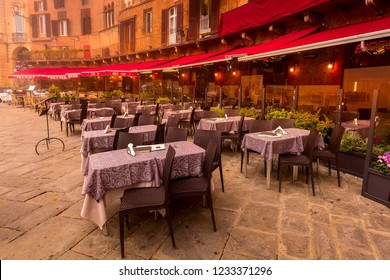 Siena, Italy - October 25, 2018: Cafe and restaurants tables at Campo Square or Piazza del Campo with Tower Torre del Mangia in Tuscany town
