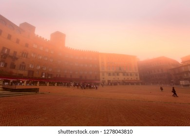 Siena, Italy - October 25, 2018: Panorama of Campo Square or Piazza del Campo with cafe, restaurants and people in Tuscany town at foggy morning