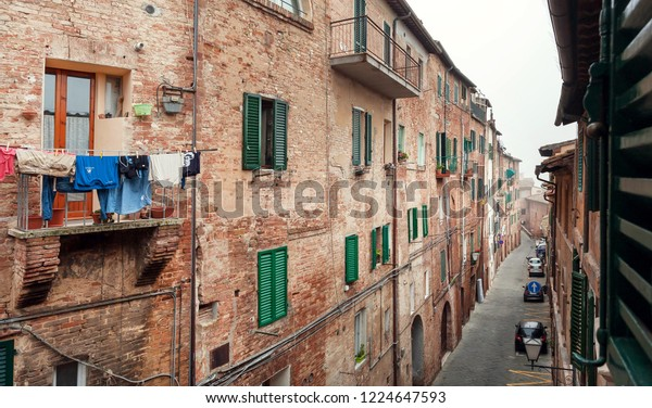 SIENA, ITALY - SEP 22: Domestic life of italians, houses with balconies and narrow streets of cities on 22 September, 2018. Historic Centre of Siena is UNESCO Heritage Site
