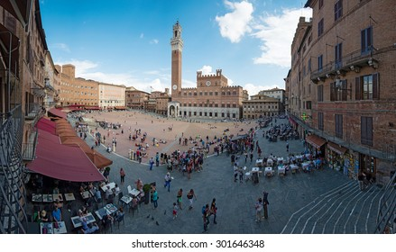 SIENA, ITALY - SEPTEMBER 17, 2014: Tourists visiting Piazza del Campo in Siena, Italy. The historic centre of Siena has been declared by UNESCO a World Heritage Site.