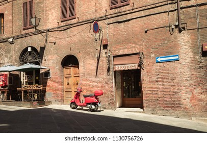 SIENA,ITALY- JUNE 18, 2018: The new red vespa is parked in area of Duuomo in Siena