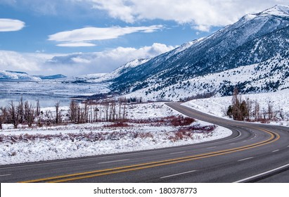 Sierra Nevada Highway in Winter:  A scenic California highway curves among snowy mountains and a frozen lake near Yosemite National Park.