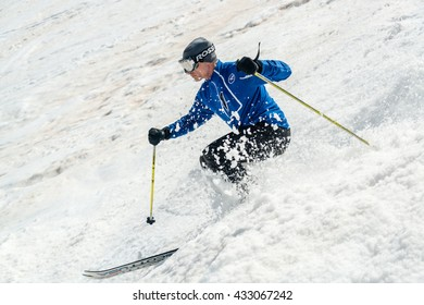 SIERRA NEVADA, SPAIN - MAY 2, 2014: A skier rides down the hill through a natural (off-piste) field of ski bumps at high speed.