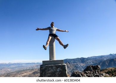 SIERRA NEVADA, SPAIN - SEPTEMBER 10, 2016: Young cheerful man raising arms and stretching legs on the top of Silleta de Padul mountain in Sierra Nevada