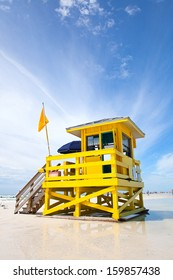 Siesta Key Beach, Florida USA, yellow colorful lifeguard house on a beautiful summer day with ocean and blue cloudy sky