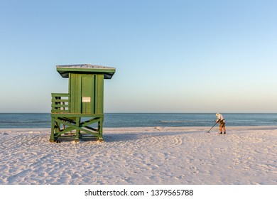 Siesta Key, FL - March 28, 2019: Beachcomber searching for loot near one of the lifeguard towers on Siesta Key Beach. The popular tourist destination has a reputation as one of America's Best Beaches.