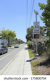 SIESTA KEY, FLORIDA - MAY 9, 2013: Your Speed, vehicle speed detector sign showing current car speed that just passed and posted regular speed limit on top just outside Siesta Beach on a sunny day.