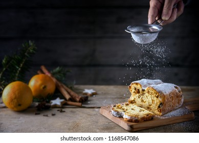 Sieving powdered sugar on a christmas cake, in germany christstollen, orange and spices blurred in the back on a rustic wooden table, dark background, copy space, selected focus, narrow depth of field