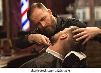 Siew form side of careful male master in process of working in barbershop. Professional barber doing trendy beardcut with razor to male customer sitting in chair. Concept of beard care and service.