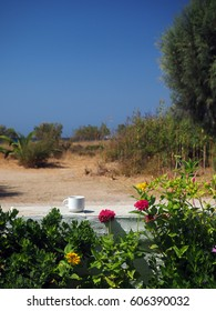 Sifnos Greek Island scene cup of coffee on white wall with autumn flowers with view of Kamares beach